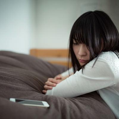 「元カレからの着信を待つ失恋女子」の写真素材