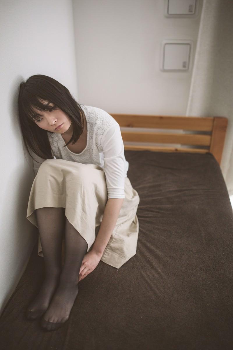 「隣室から漏れ聞こえる笑い声に耳を傾けるネガ女」の写真[モデル:たけべともこ]