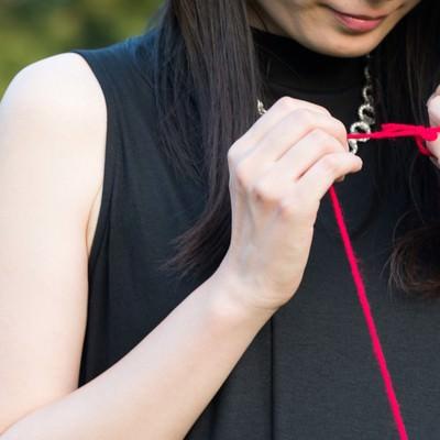 「赤い糸で結ばれた女性」の写真素材