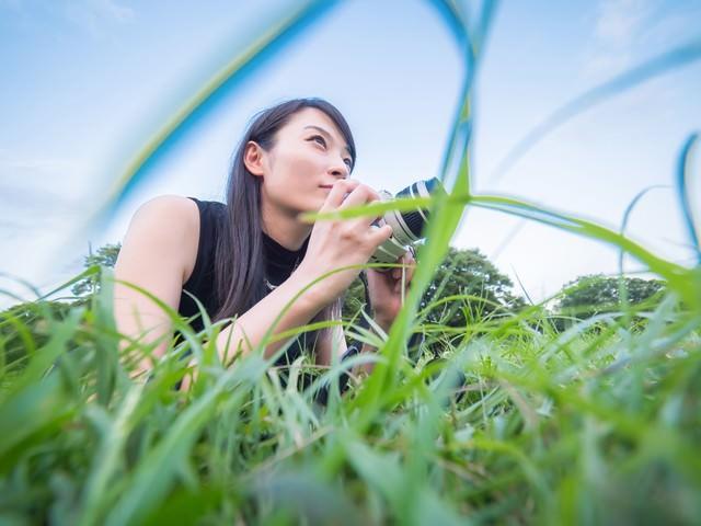 ローアングルから撮影するカメラ女子の写真