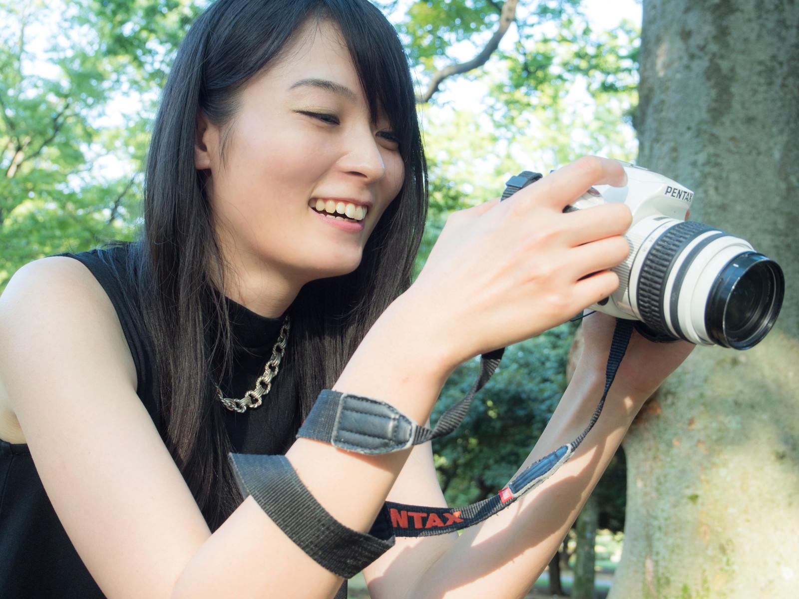 「撮った写真を確認している一眼女性」の写真[モデル:たけべともこ]