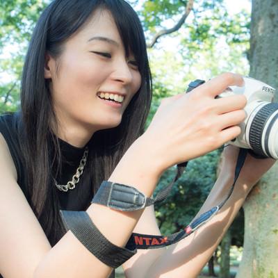 撮った写真を確認している一眼女性の写真