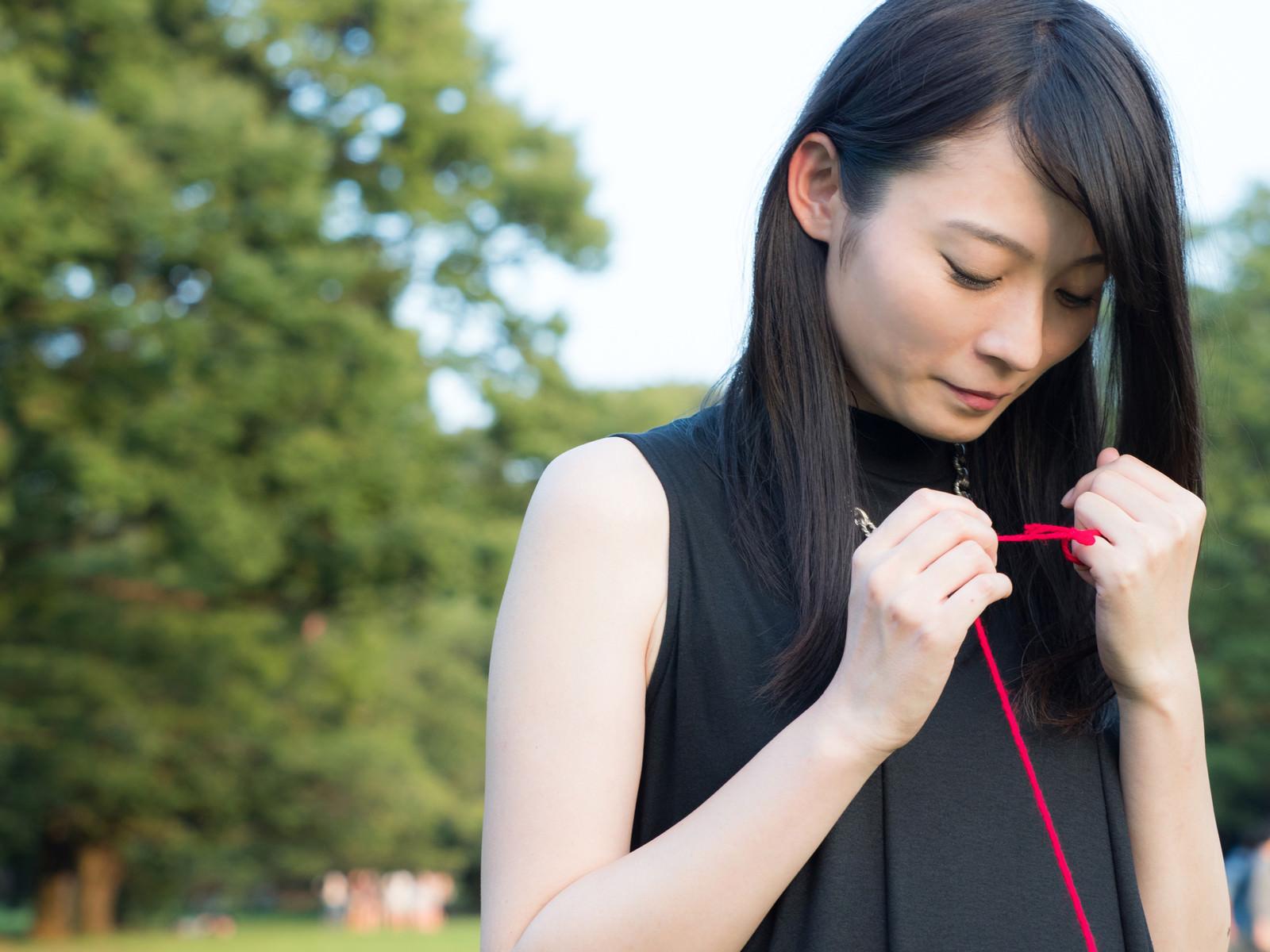 「ちぎれた赤い糸を結び直す女性」の写真[モデル:たけべともこ]
