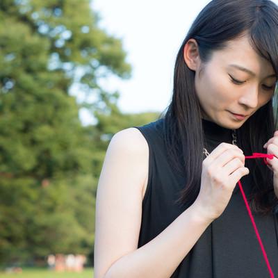 「ちぎれた赤い糸を結び直す女性」の写真素材