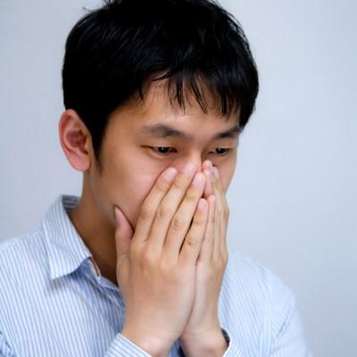 「青ざめて口元に手をやる男性」の写真素材