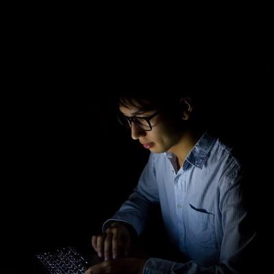 「暗闇でPCを使う男性」の写真素材