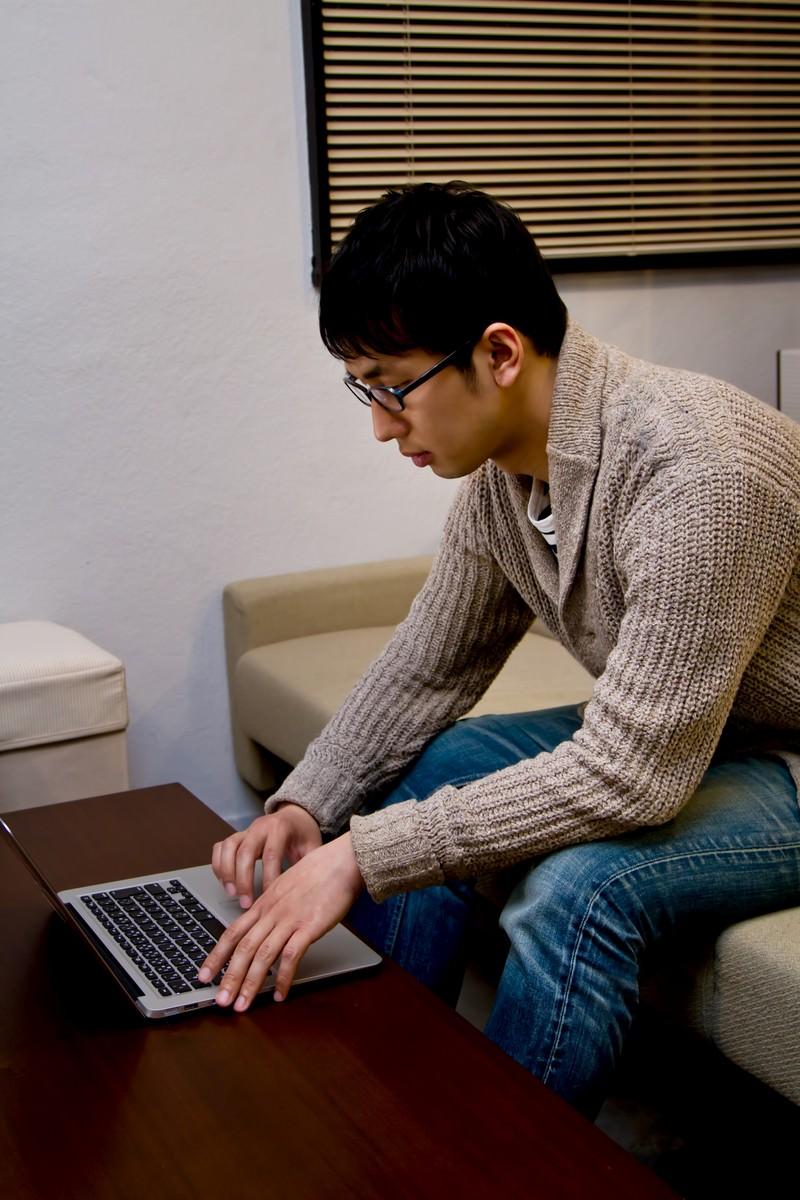 「ソファーでPCを触るデザイナーの男性」の写真[モデル:大川竜弥]
