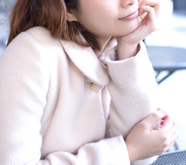頬杖をつくコートを着た女性の写真