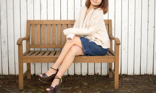 ベンチに腰掛ける若い女性の写真