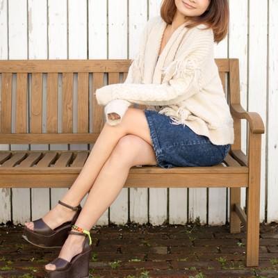 「ベンチに腰掛ける若い女性」の写真素材