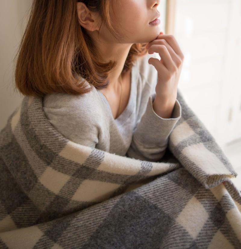 冷え性でブランケットを羽織る女性
