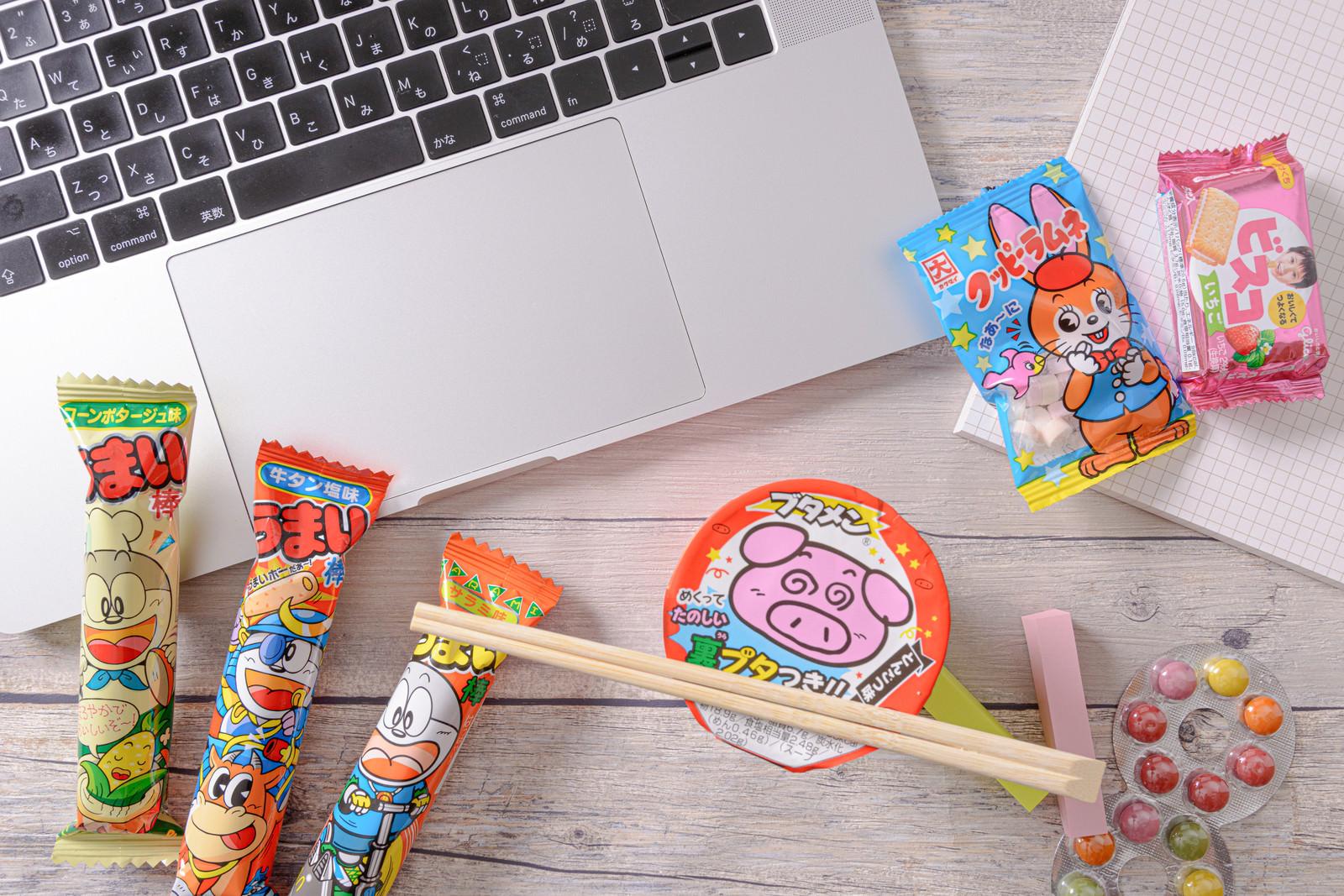 「ブタメンを囲むお菓子とノートPC」の写真