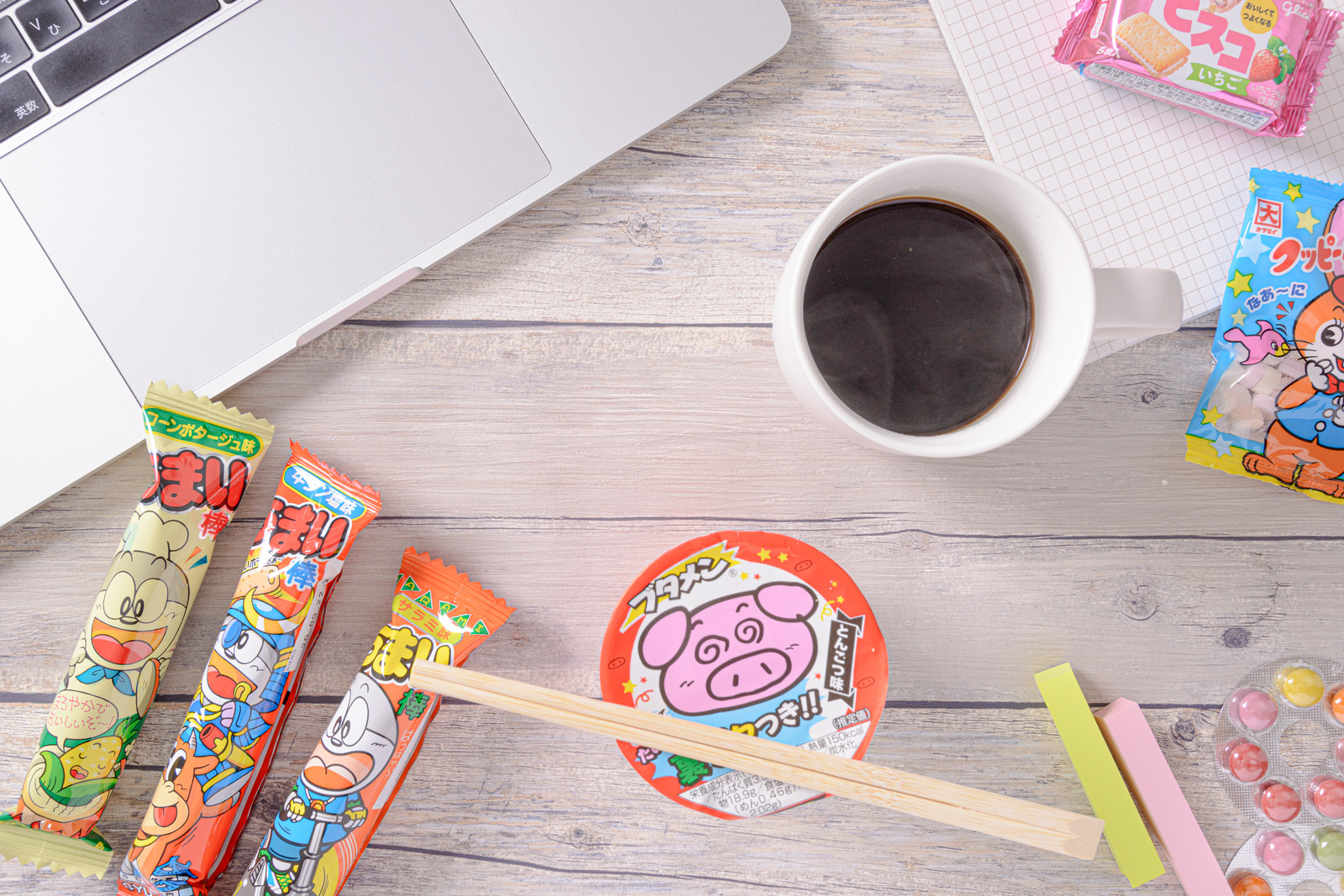 「コーヒーとブタメンの周りに散らばるお菓子類」の写真
