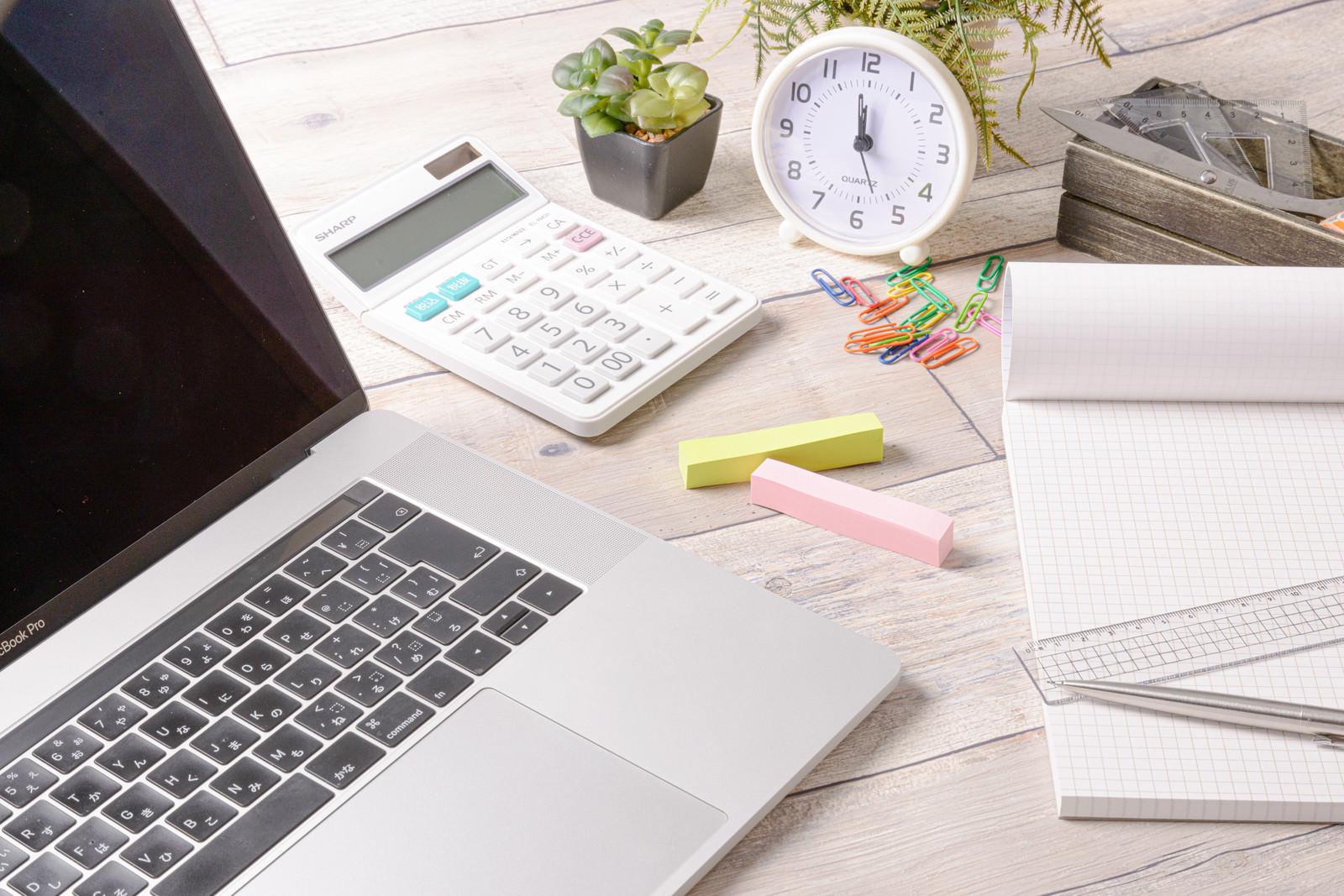 「デスクに置かれた文具とノートパソコン」の写真