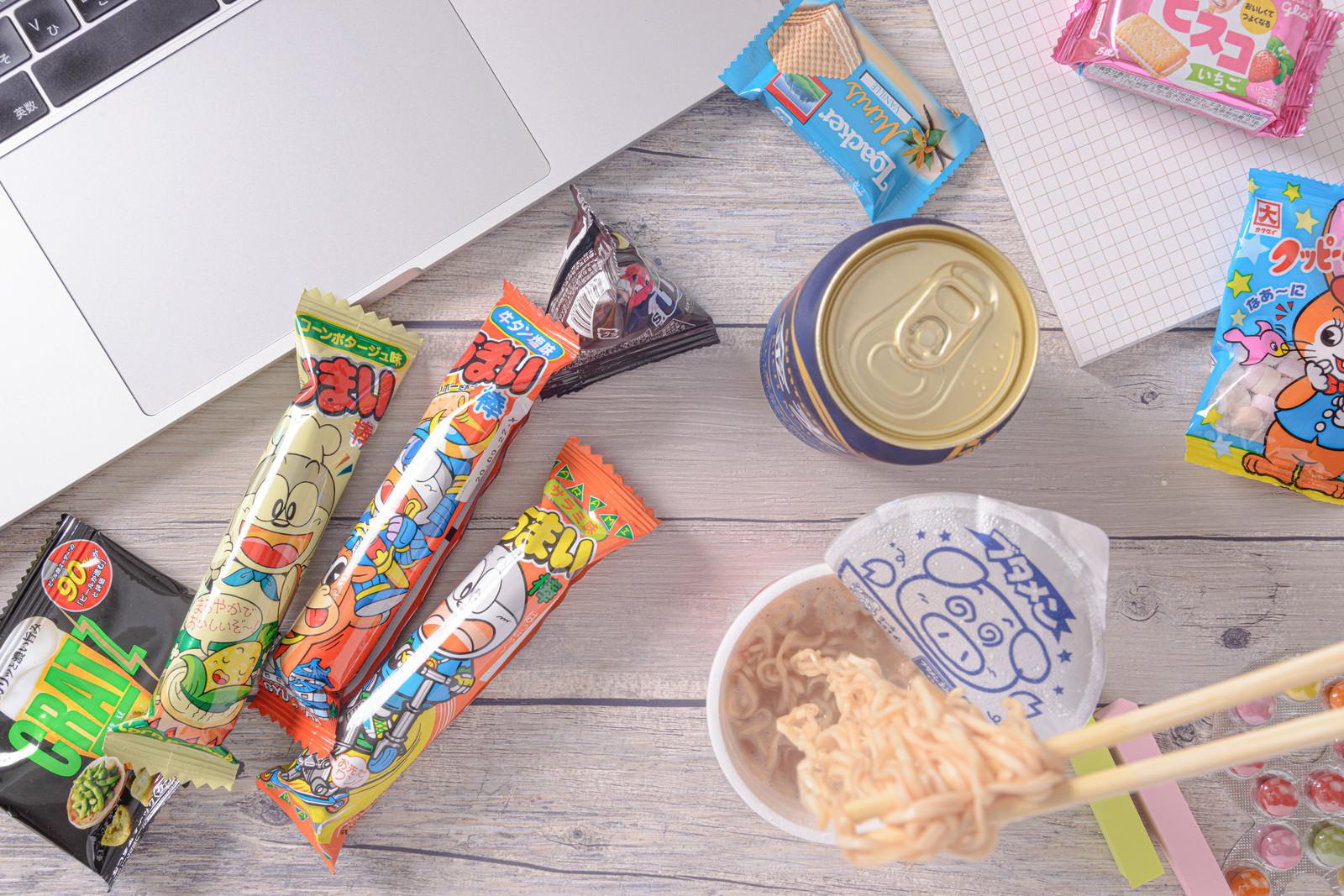 「食べかけのブタメンと散らばったお菓子」の写真