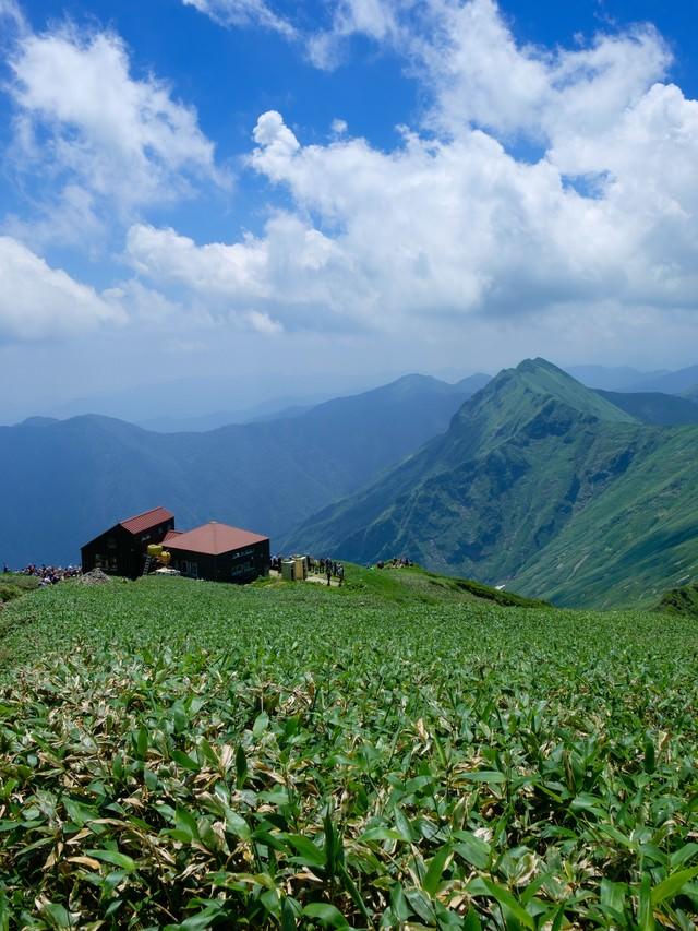 登山道に現れた山小屋と山峰の風景の写真
