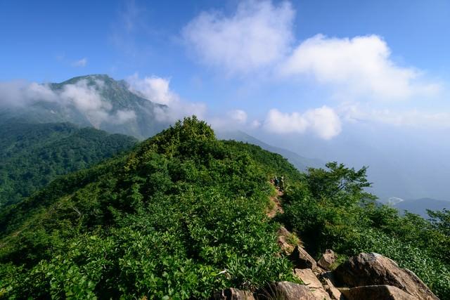 沸き立つ雲に隠れる山頂と登山者の写真