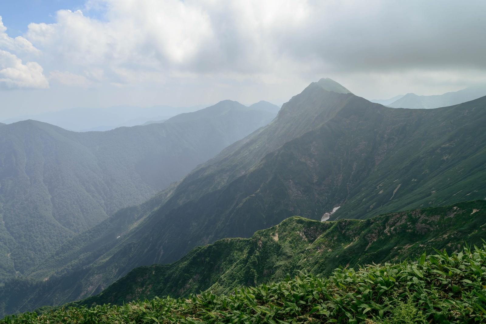 「雲が沸き立ち峰々が陰る風景」の写真