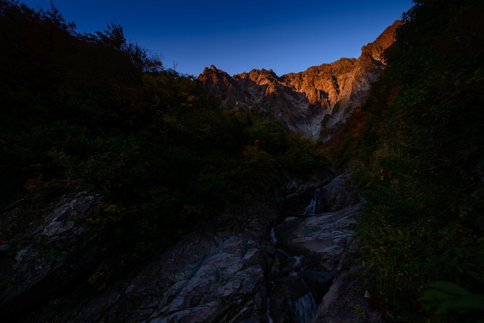「朝日を浴びる巨大な岩壁(一ノ倉沢)」の写真