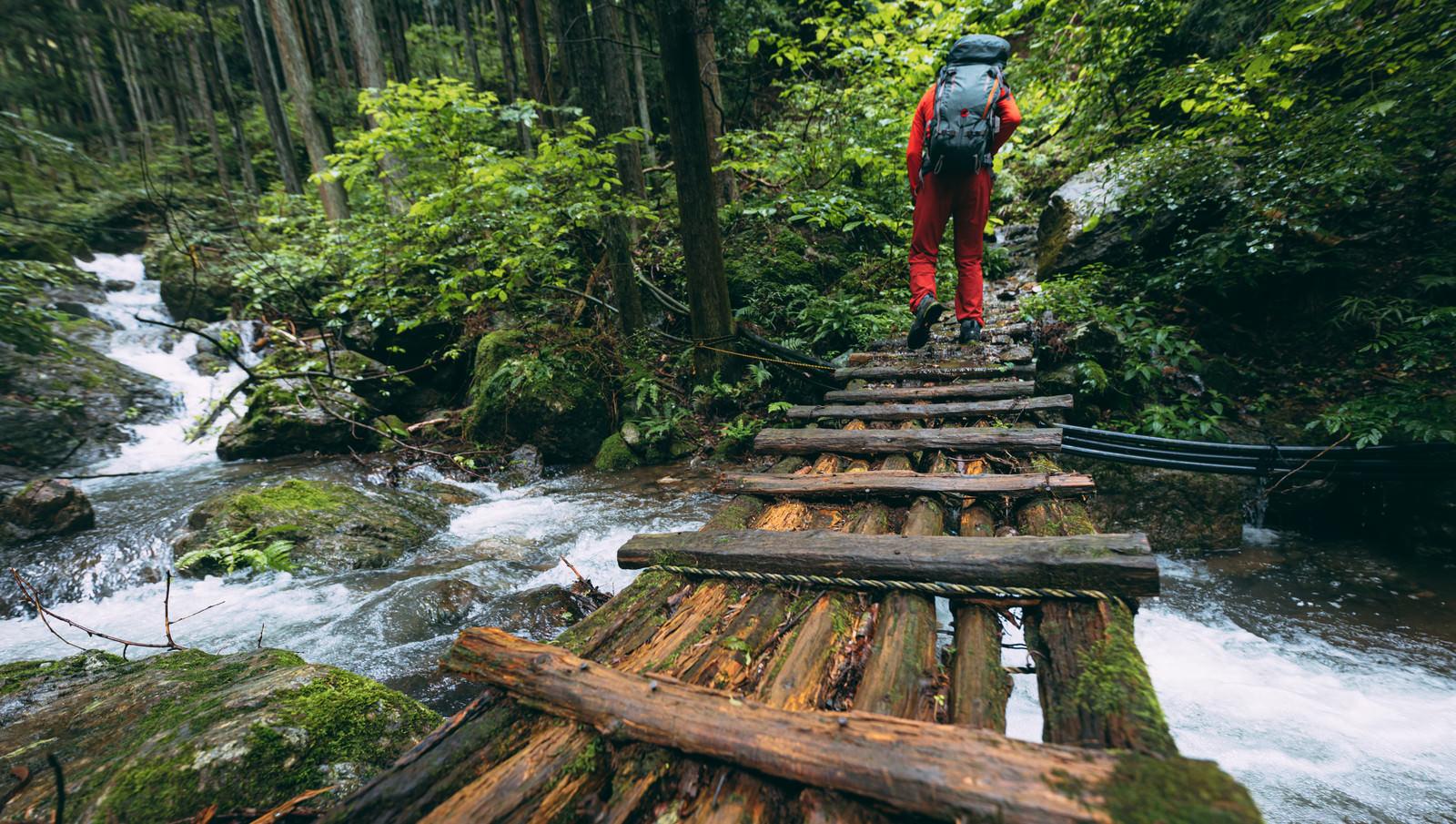 「渓流にかかる木製の橋を渡る登山者」の写真