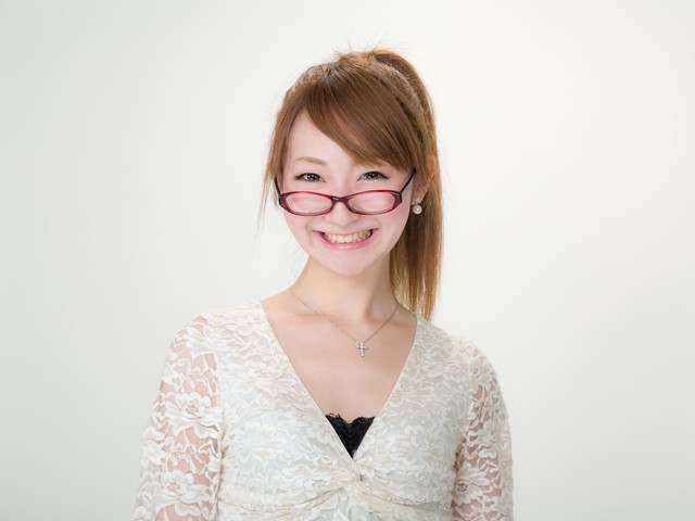 眼鏡をずらしてにっこり微笑む女性の写真