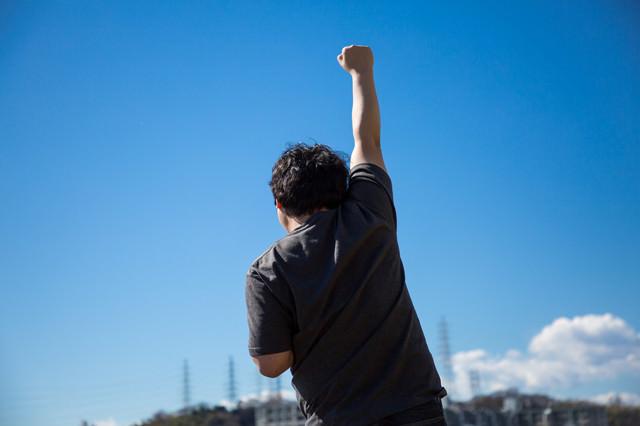 独り屋外で鼓舞する男性の後ろ姿の写真