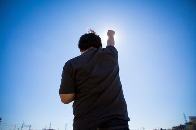 太陽に向かって拳を高々とあげる後ろ姿
