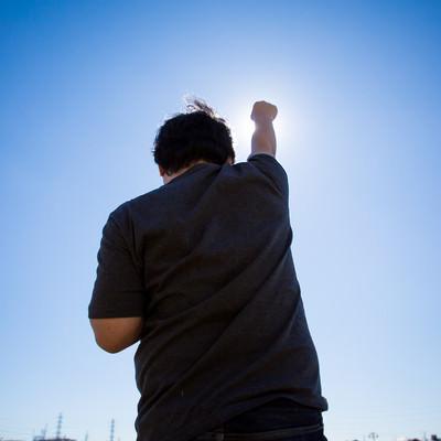 「太陽に向かって拳を高々とあげる後ろ姿」の写真素材