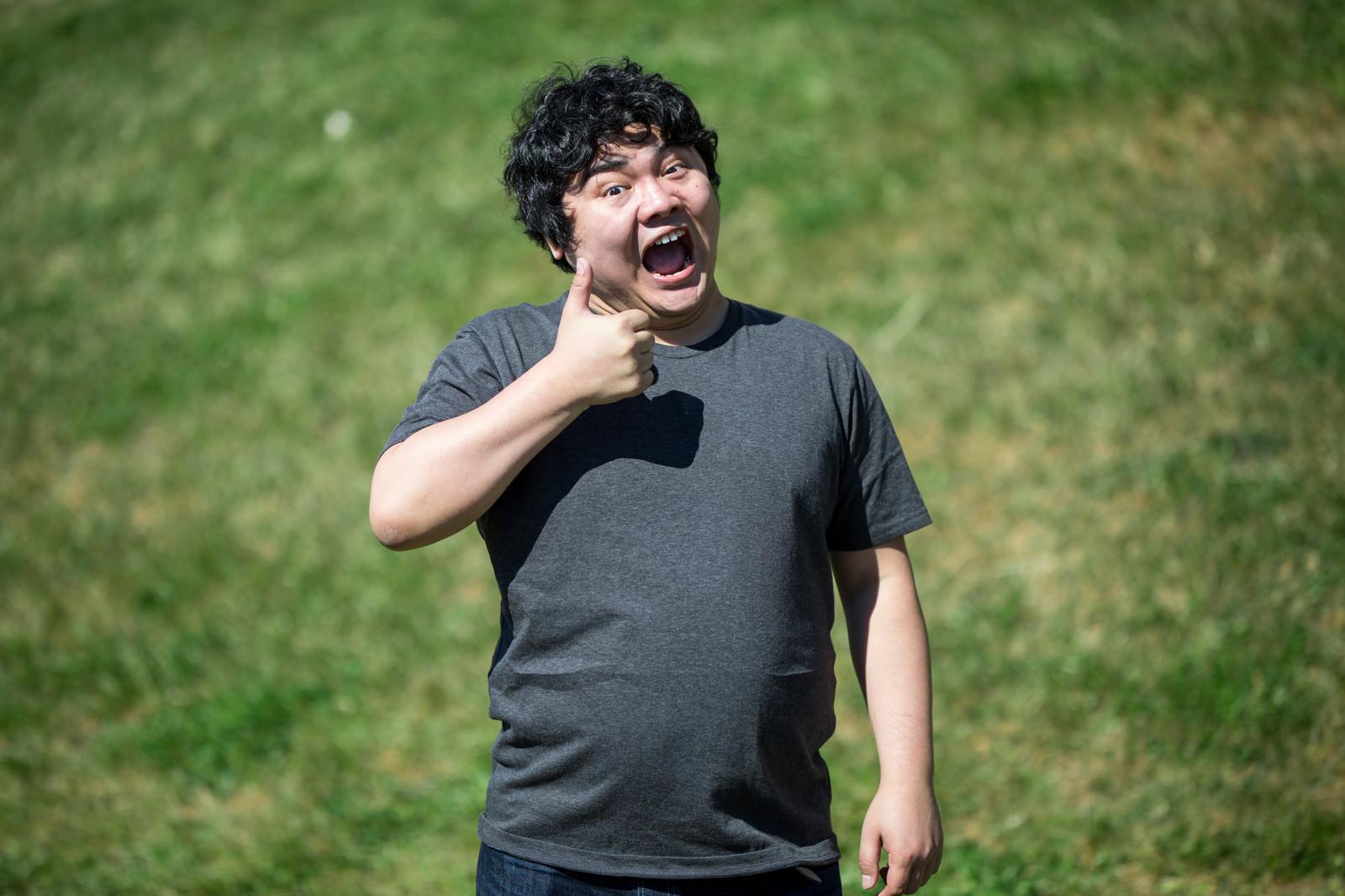 「コードレビューに最高の笑顔でサムズアップする男性」の写真[モデル:段田隼人]
