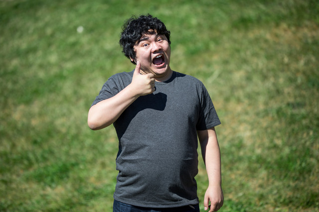 コードレビューに最高の笑顔でサムズアップする男性の写真