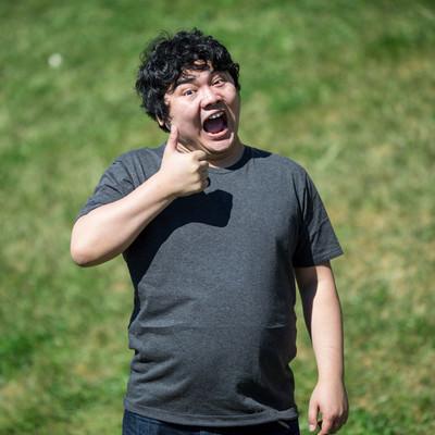 「コードレビューに最高の笑顔でサムズアップする男性」の写真素材