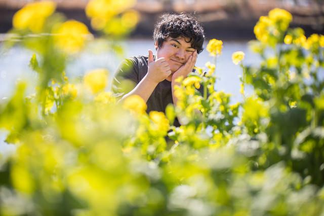 菜の花畑とサムズアップの写真