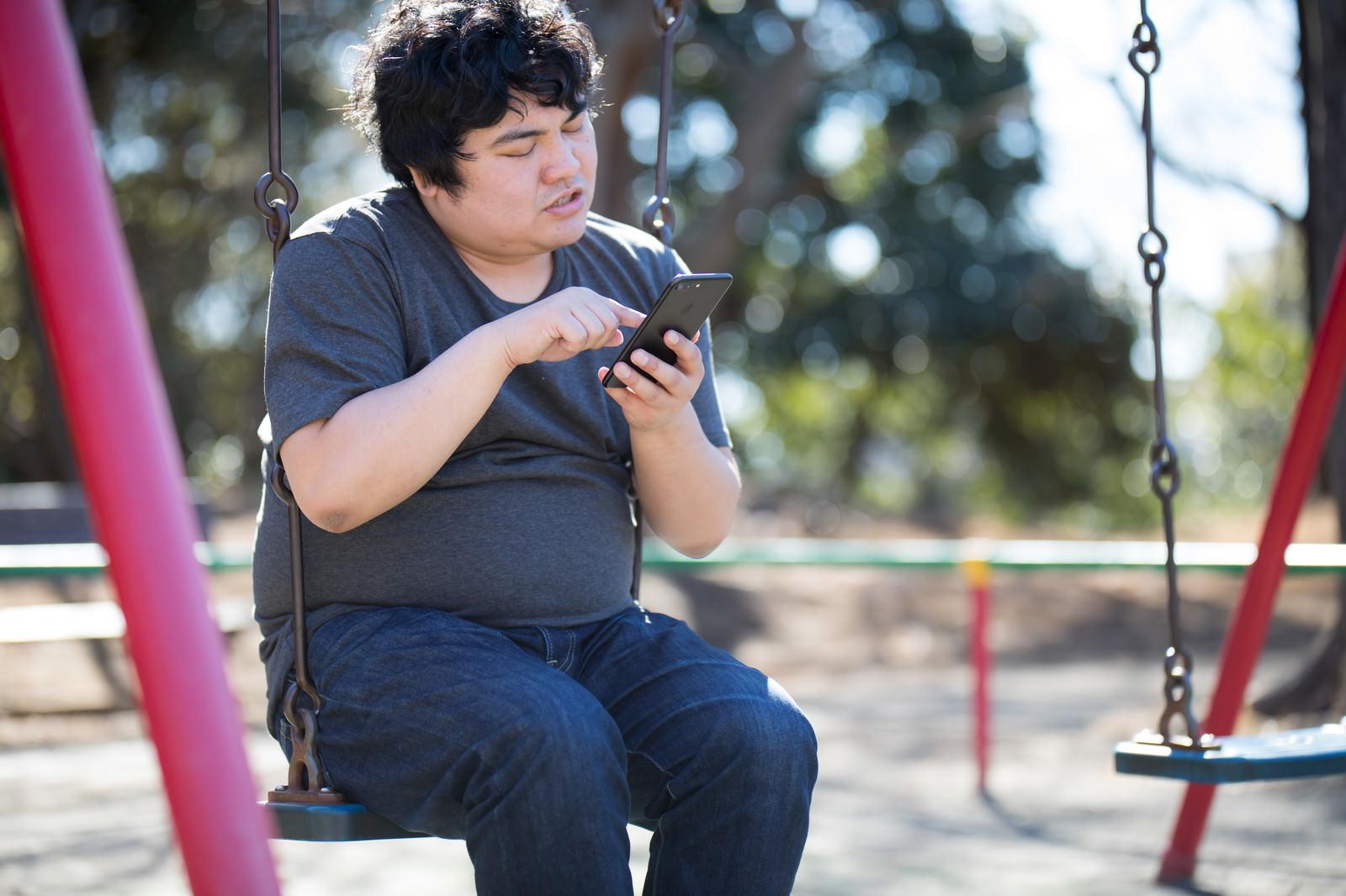 「仕事をサボってスマホゲームに熱中する廃課金者」の写真[モデル:段田隼人]