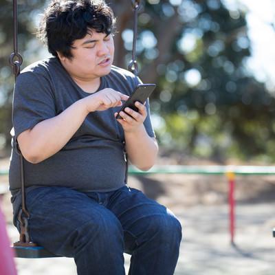 「仕事をサボってスマホゲームに熱中する廃課金者」の写真素材