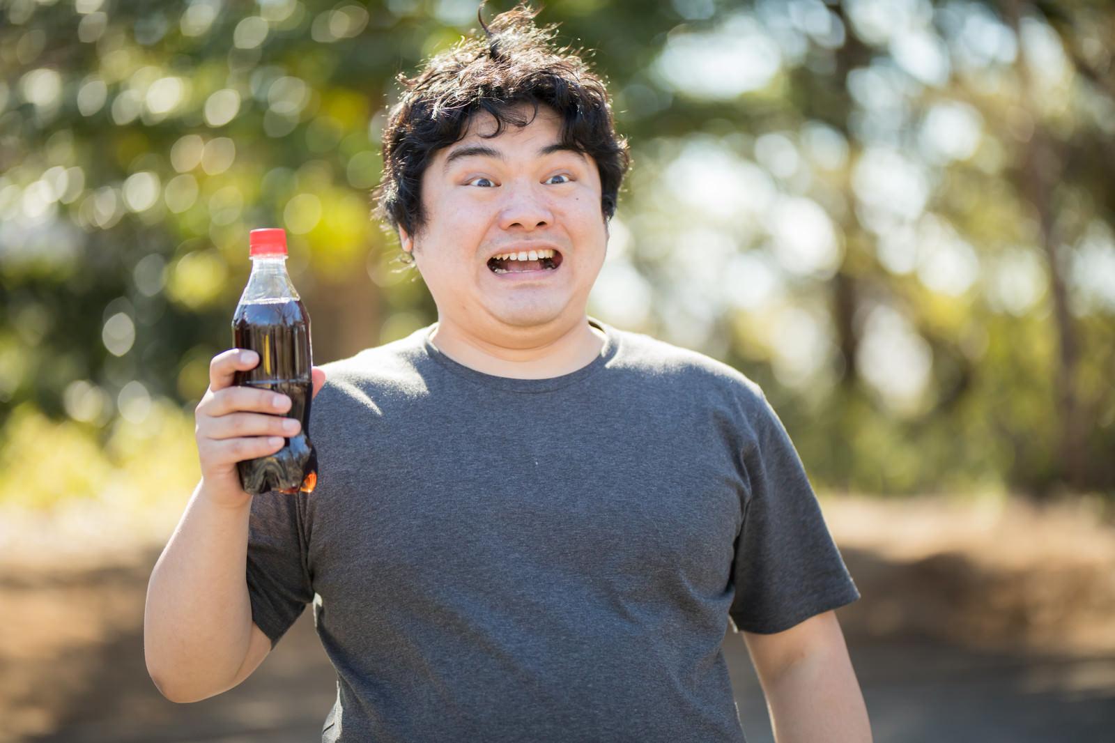 「コーラ片手に不気味な笑みを浮かべる太っちょさん」の写真[モデル:段田隼人]