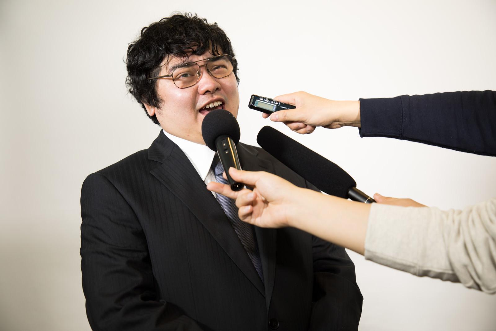 「疑惑をマスコミに詰められる役員」の写真[モデル:段田隼人]