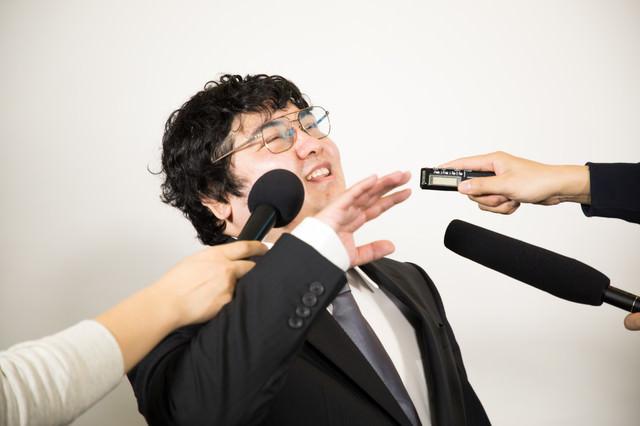 執拗な囲み取材を受ける男性の写真