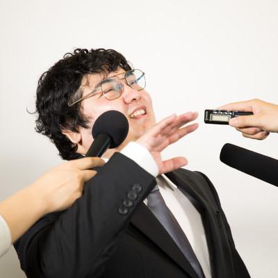 「執拗な囲み取材を受ける男性」の写真素材