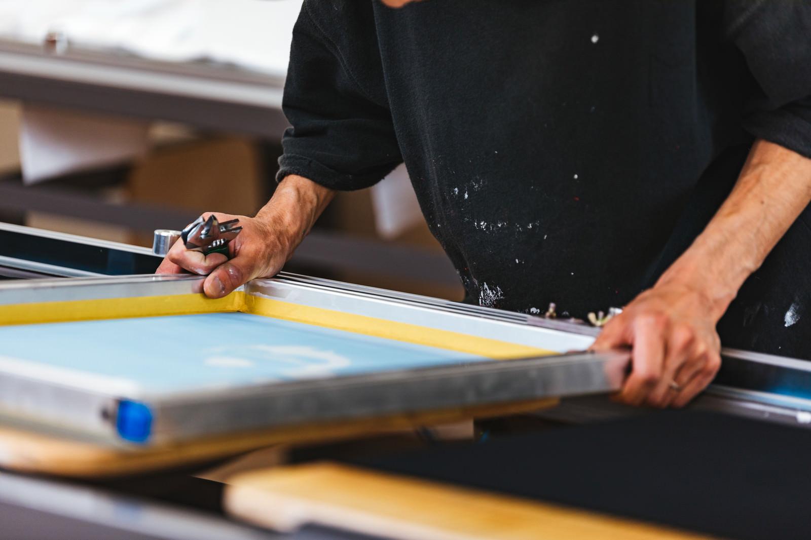 「シルク印刷のプリント位置を合わせる職人」の写真