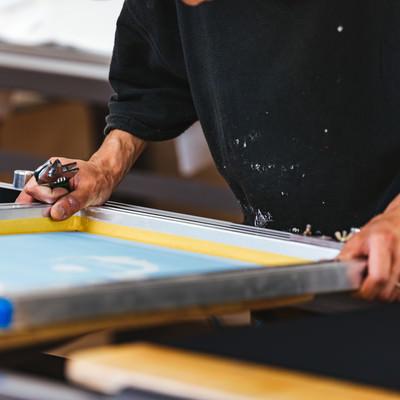 シルク印刷のプリント位置を合わせる職人の写真