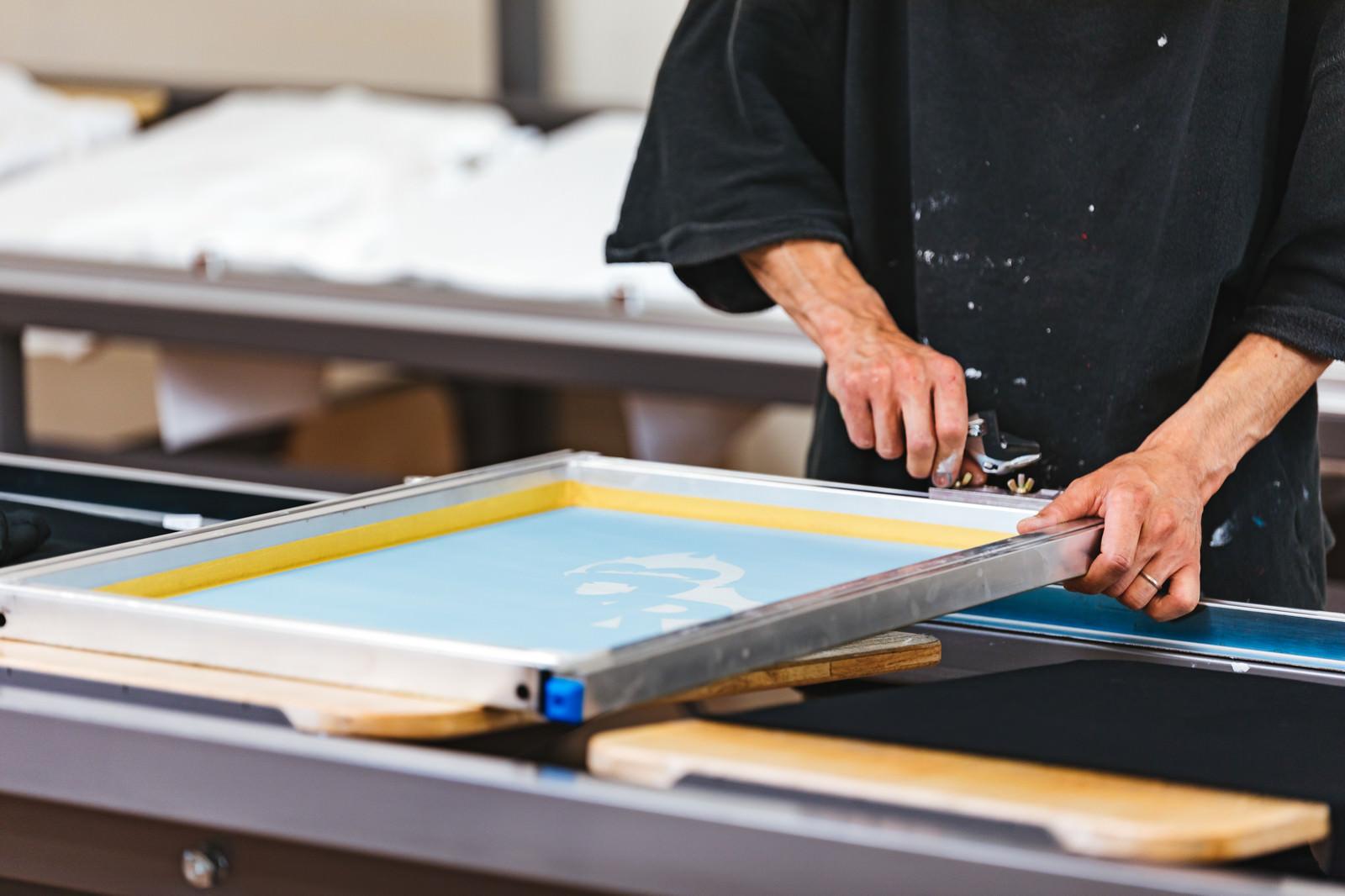 「シルク版の位置を調整する職人」の写真