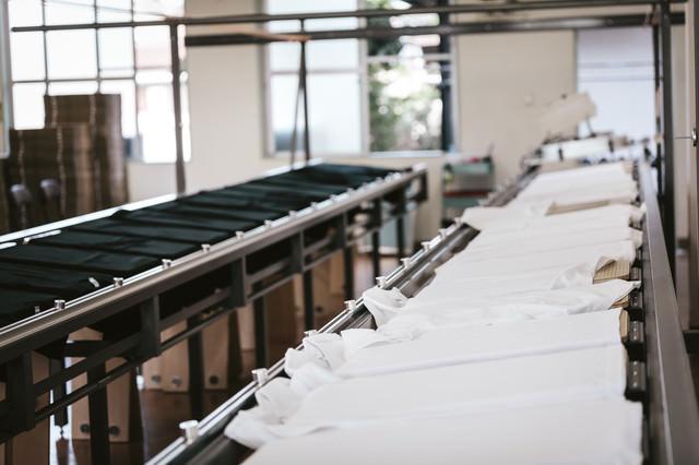 作業台に並ぶ白と黒のTシャツ(シルクスクリーン印刷)の写真