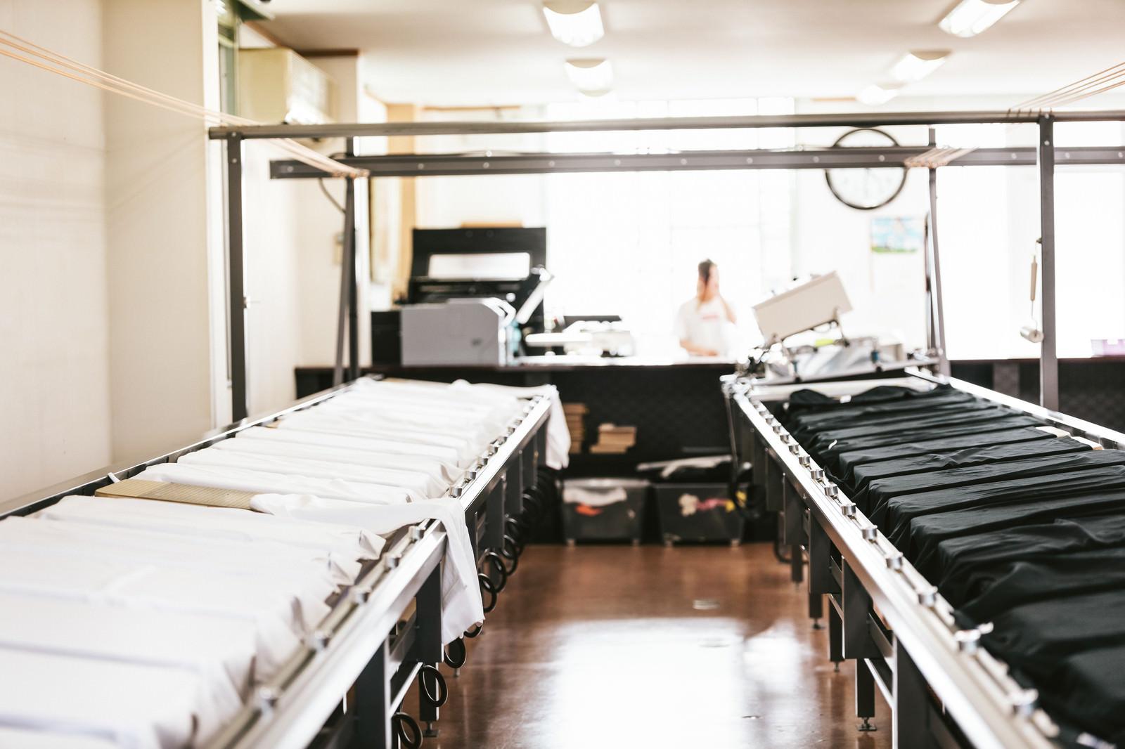 「シルクスクリーン印刷の台に置かれた白黒のティーシャツ」の写真