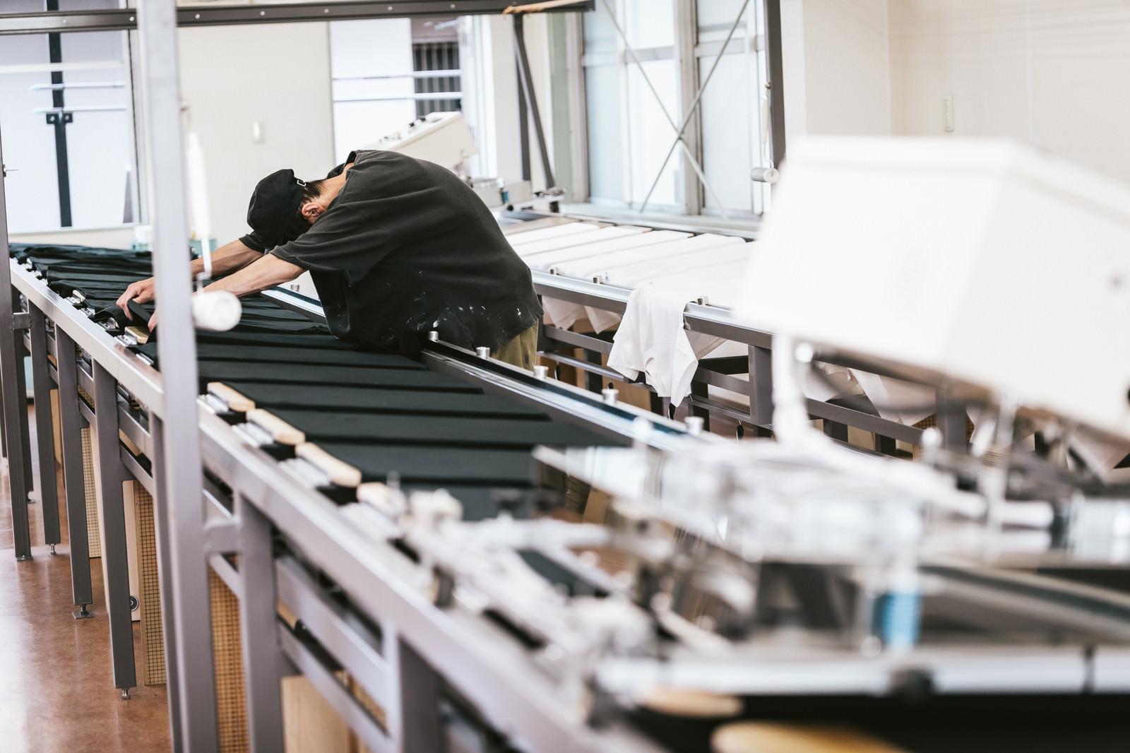 「シルク印刷台にTシャツを並べる職人」の写真