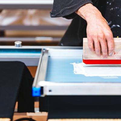 シルクスクリーン印刷を行なう職人の手元の写真