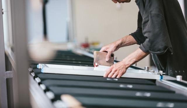 塗っては乾燥させる作業を繰り返すシルク印刷の様子の写真