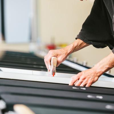 スキージを使って何度も着色する職人(シルクスクリーン印刷)の写真
