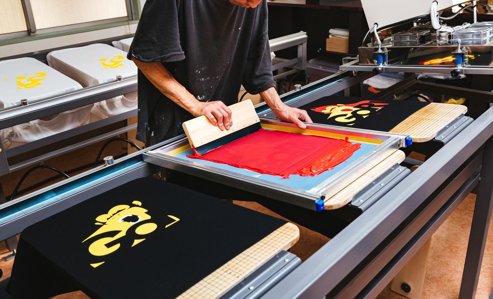 「シルク版のインキを黒いTシャツに着色してい様子 | 写真の無料素材・フリー素材 - ぱくたそ」の写真