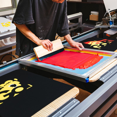シルク版のインキを黒いTシャツに着色してい様子の写真