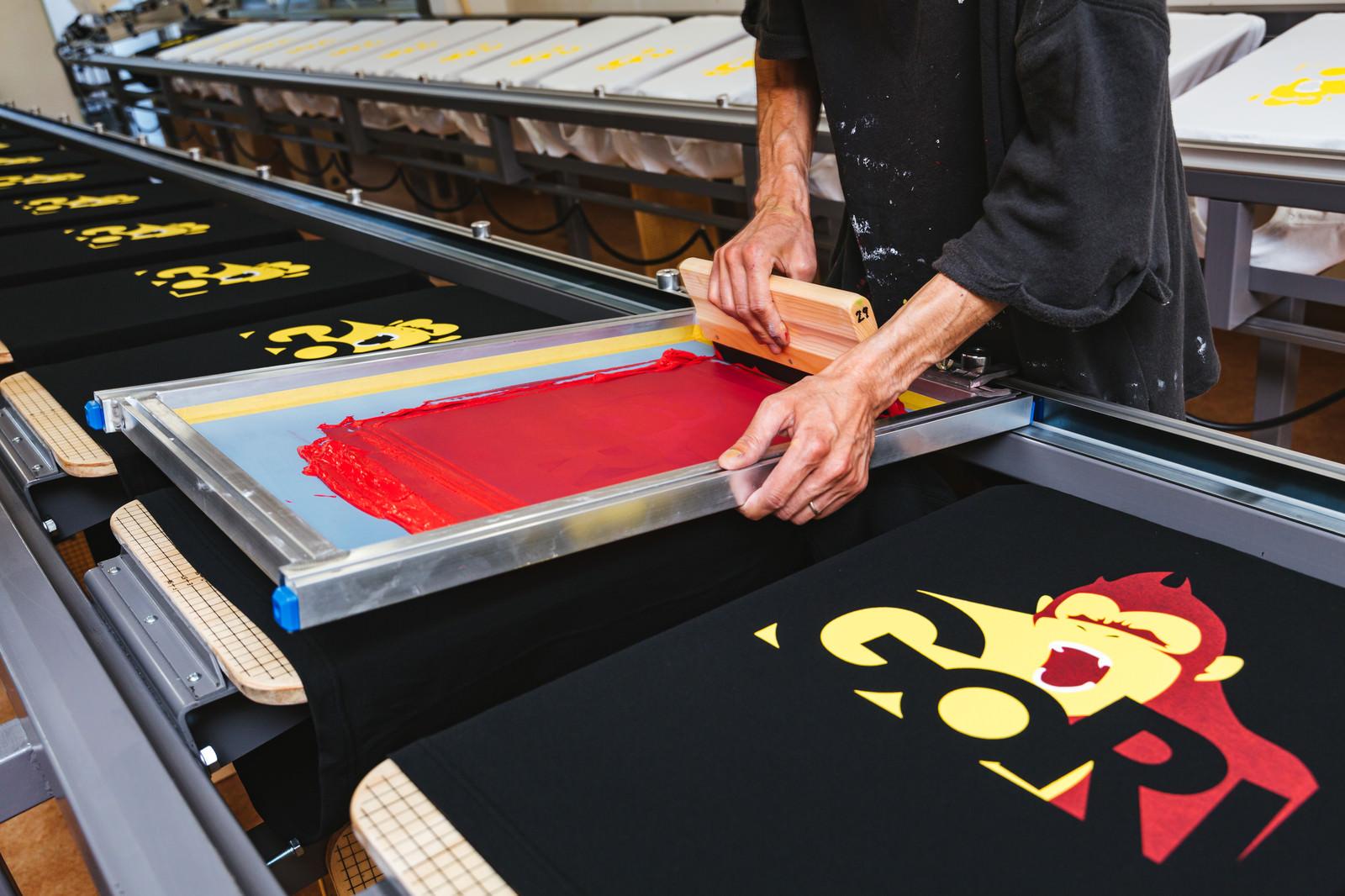 「手刷りでTシャツに着色するシルクスクリーン印刷の現場」の写真